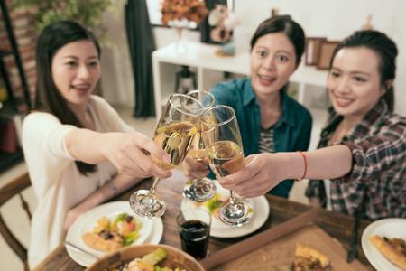 友人はシャンパングラスを乾杯し、楽しい応援を楽しむ - 若者はホームパーティーで一緒に収穫の時間を楽しむ - 若者と友情の概念 写真素材