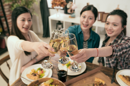 Friends hands toasting champagne glass and having fun cheering - Young people enjoying harvest time together at home party - Youth and friendship concept