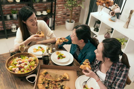 top view of the group of people enjoys pizza together at home.
