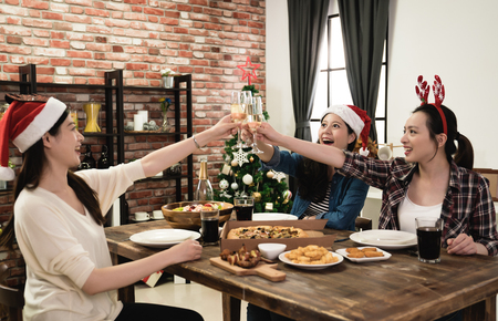 three Asia young girl friends holding the glass of champagne celebrating Christmas at home Stockfoto