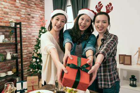 beautiful young Asia girls showing Christmas gift box and enjoy dinner together.