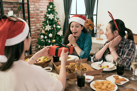 group of young asia girl exchange Christmas gift box on Christmas Eve day at home. Stock Photo