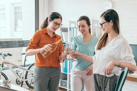 Group of happy business women holding flutes with champagne and smiling while standing close to each other indoors. We got a contract concept. Stock Photo