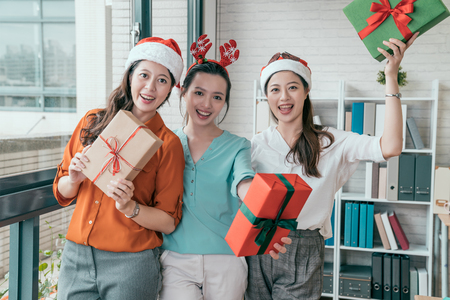 group of three people wearing red Santa hat and holding gift box in the office.