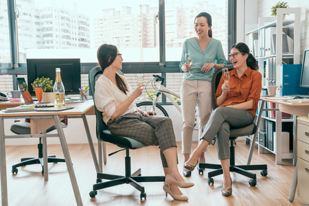 Successful team celebrates concept. Group of cheerful young people discussing something with smile while sitting or standing in office Stockfoto