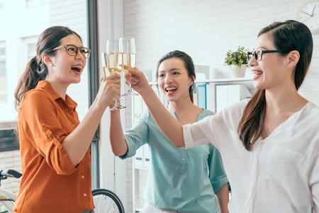 Group of happy business asia team toasting with champagne in the office