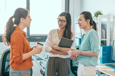 De jonge mooie vrouw die van Azië en iets gesturing bespreken terwijl haar medewerkers die aan haar zitten die bij de bureaulijst luisteren. Goede beslissingen nemen. Stockfoto