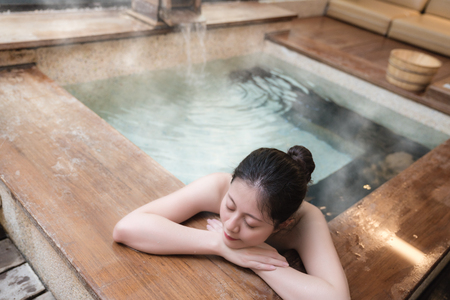 she really enjoys! beautiful young girl stay on wooden poolside hot springs while steam water on the background.