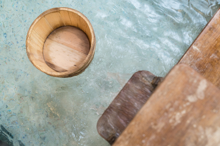 japanese style hot springs with wooden barrel scoop floating on water and water flowing. Stock Photo