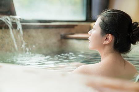 魅力的な女の子の裏側の眺めは温泉水に滞在し、景色を楽しむ