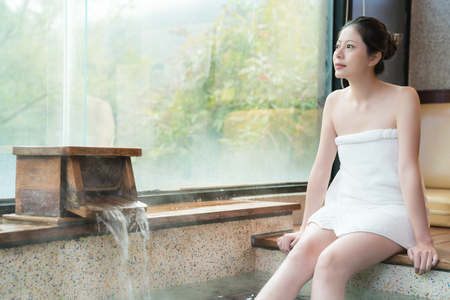 beautiful young asian womn enjoy the hot spring look outside and sitting on poolside