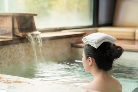 rear view of young girl enjoy the hot springs and put a towel on her head while water flows on the background. Stock Photo