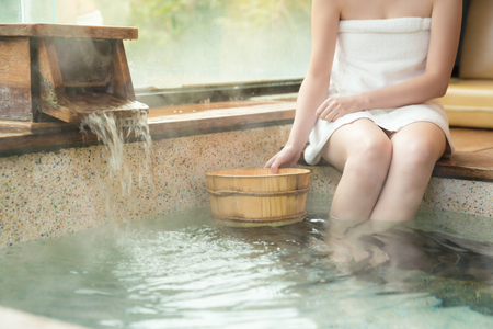 woman holding the wood barrel scoop and sitting on poolside Reklamní fotografie