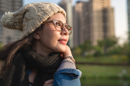 charming girl student enjoys the urban view and love the sunny weather in the winter.