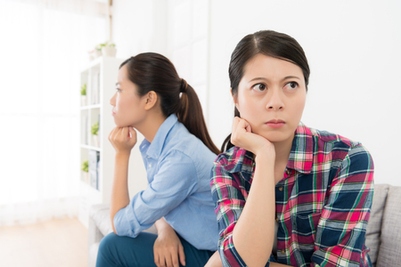 Young pretty girl with her best friend having quarrel feeling angry sitting on sofa together giving each other silent treatment. selective focus photo. Stock Photo