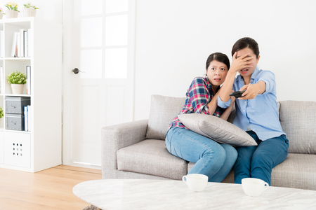 young elegant female friends watching tv together and choosing ghost program video feeling afraid when they sitting on sofa couch. Stock Photo