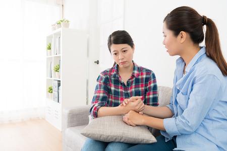 mooi meisje kijkend naar droefheid vrouw praten op bank in de woonkamer en houdt haar handen comfort in de hoop dat ze gelukkig kan na breken.