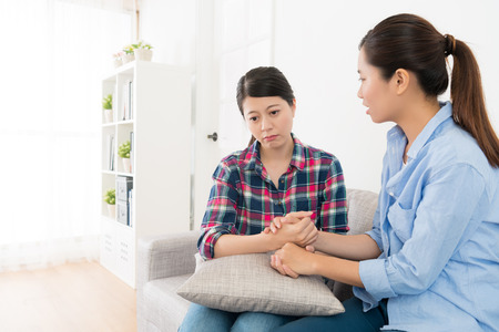 piękna dziewczyna patrząc na smutek kobieta rozmawia na kanapie w salonie i trzymając ręce komfort mając nadzieję, że będzie szczęśliwa po zerwaniu.