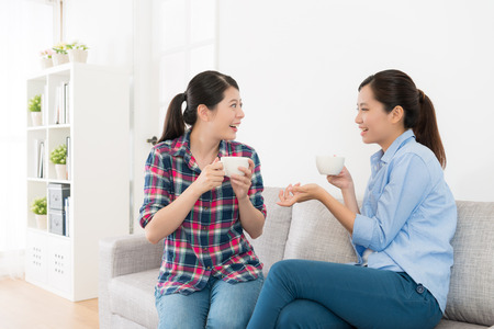 leisurely pretty girls sitting on living room sofa talking together and drinking hot coffee chatting enjoying afternoon tea time.