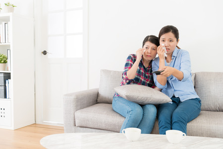Attractive young female friends watching tv show and feeling sad crying sitting on sofa couch. Stock Photo