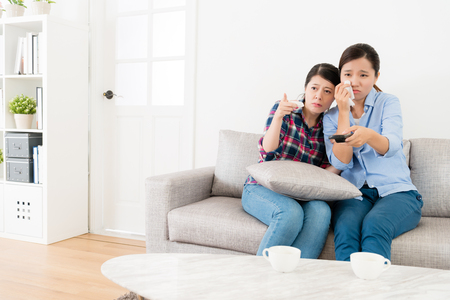 beautiful pretty sisters sitting on sofa couch crying when they watching television program finding sadness video story.