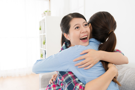 Happy female friends hugging together in living room and cheerfully celebrate about the successful finished college class. Фото со стока