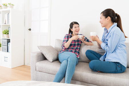 happy pretty woman talking with her best sister and enjoying tea time together during leisurely holiday in living room at home.