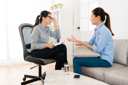 pretty elegant woman sitting on sofa couch talking with her doctor and psychologist lady carefully listening think how to treatment.