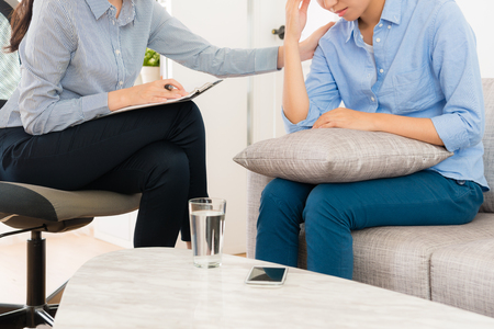 professional female psychologist working with teenage girl in office and talking with her assistant to therapy depression sickness. Standard-Bild