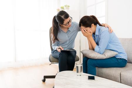 hermosa niña bonita sentada en el sofá llorando cuando ella habla con el médico y el psicólogo consolándola en la oficina de la clínica.