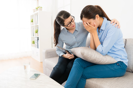 smutek przygnębiona kobieta mająca problemy psychologiczne siedząca na sofie płacząca, a jej doradca patrzy na nią, próbując się pocieszyć.