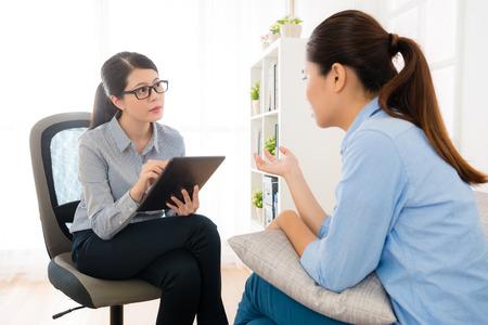 Doutor fêmea novo bonito do psicólogo que usa a tabuleta digital móvel que grava toda a informação de sua fala paciente. Foto de archivo