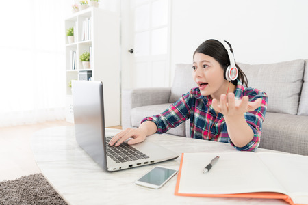 beautiful pretty female student trying to speak english loudly when she looking at computer using online e-learning system studying at home. Stock Photo