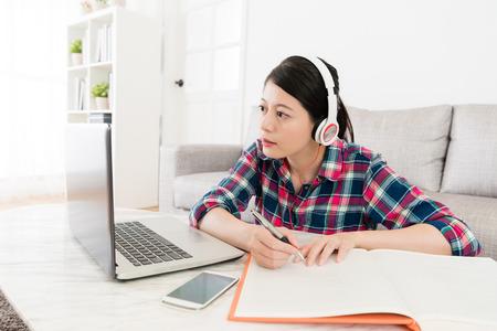 Estudante fêmea consideravelmente bonito que veste o auriculares que senta-se na sala de visitas e que usa o portátil móvel através do estudo do sistema do ensino eletrónico. Foto de archivo