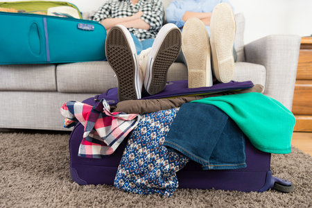 closeup of two people put legs on luggage suitcase with many messy clothing and sitting on sofa couch talking discussing travel plan.