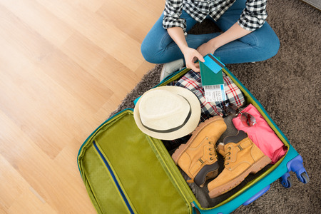 high angle view photo of young woman sitting on living room floor packing luggage showing boarding card and passport with credit card. Stok Fotoğraf