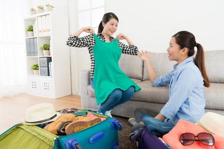 友人のための服のドレスを示し、彼らは自宅で荷物を梱包するとき、リビングルームで旅行計画を議論する幸せな笑顔の女性。