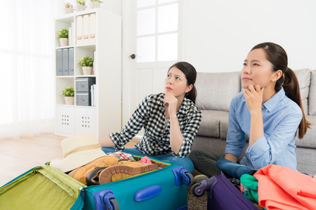 Beautiful pretty women ready to travel together and sitting in living room packing luggage thinking something not preparing yet.