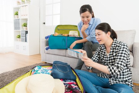 Smiling beautiful woman holding air ticket talking with young girl explaining boarding time and packing luggage in living room.