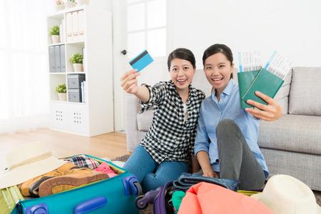 행복 한 아름 다운 여성 신용 카드 및 여권 전자 상거래를 보여주는 항공 티켓을 들고 카메라를 찾고 여행 일정 개념을 구입.