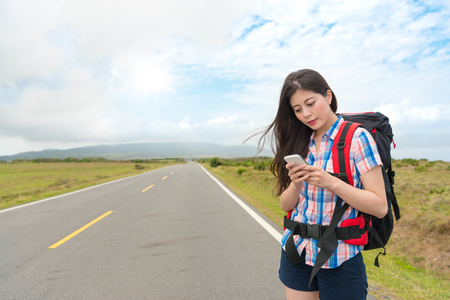 young lovely female traveler standing on asphalt roadside using mobile cell phone to searching local information during holiday travel.