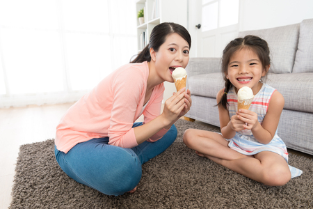 mom with her happy daughter relaxing on living room floor and looking at camera eating ice cream. Banque d'images
