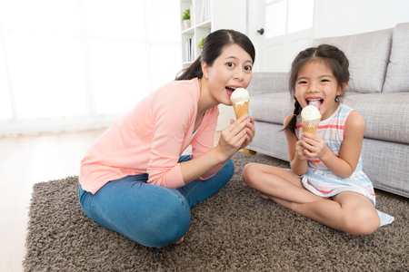 cheerful leisurely mother with little girl eating ice cream together sitting on living room floor and face to camera showing enjoying summer concept.