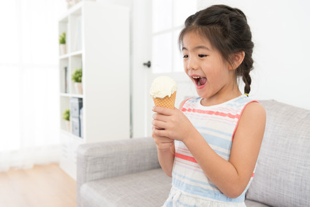 happy cheerful little girl kid holding ice cream snack sitting on living room sofa and feeling surprised during summer season holiday.