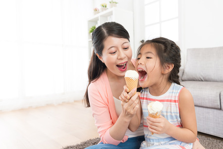 cheerful family of beautiful mother with cute daughter eating ice cream at home and playing fun together in living room.