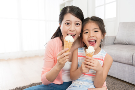 closeup photo of happy woman with little girl sitting on living room floor eating ice cream together and looking at camera laughing.