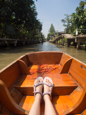 young woman wearing sandals sitting on canal boat and enjoying river view in floating market during asia thailand travel vacation.