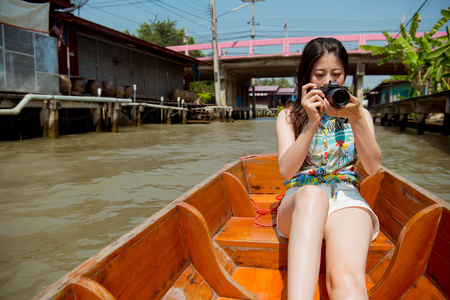 Elegant attractive woman traveler sitting on river boat in Thailand and using camera helping her travel partner taking picture. Stock Photo