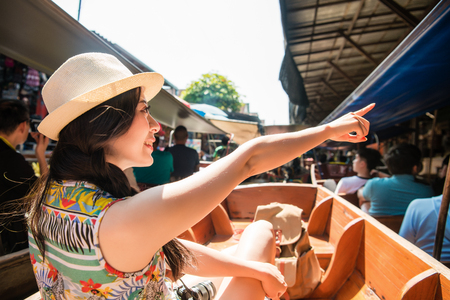 Smiling young travel woman take on river boat and pointing local vendors sharing for friend when she travel in Thailand visiting Damnoen Saduak floating market. Stock Photo