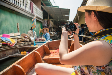 Pretty elegant woman tourist using camera taking picture when she visiting famous river Damnoen Saduak floating market in Thailand.